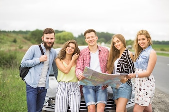 Portrait of tourist friends holding map standing in front of car at outdoors