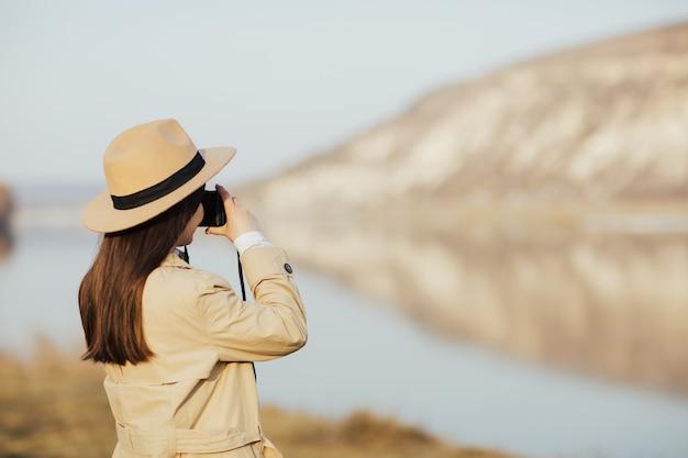 모자와 트렌치 코트에 관광 여자의 초상화는 산에서 여행하는 동안 레트로 카메라에 사진을 찍습니다.