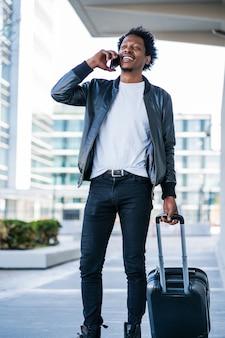 通りを屋外で歩きながら電話で話し、スーツケースを運ぶ観光客の男性の肖像画