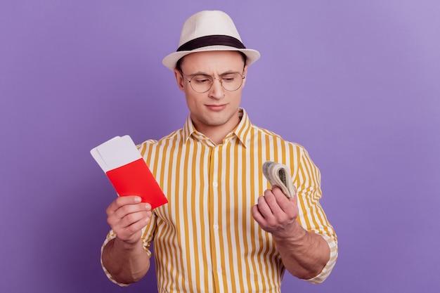Портрет туристического неуверенного парня, держащего билеты наличными банкнотами, думает об оплате на фиолетовом фоне