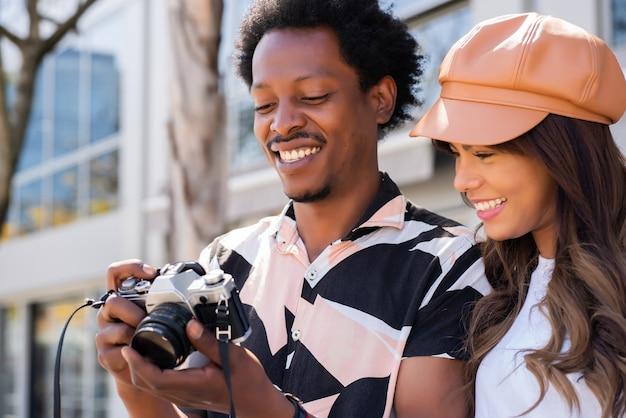 Портрет молодой пары туристов с помощью камеры и фотографирования в городе. концепция туризма.