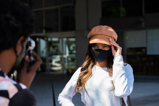 街で写真を撮っている間保護マスクを着用し、カメラを使用して観光の若いカップルの肖像画