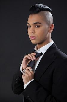 Портрет трансгендера поправляя галстук