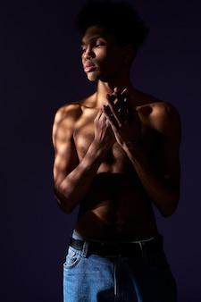 벌거벗은 몸통이 있는 트랜스젠더 히스패닉 모델의 초상화 그림자에 서 있는 트랜스젠더 젊은 남자