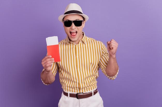 Портрет сумасшедшего парня-путешественника с билетами празднует победу на фиолетовом фоне