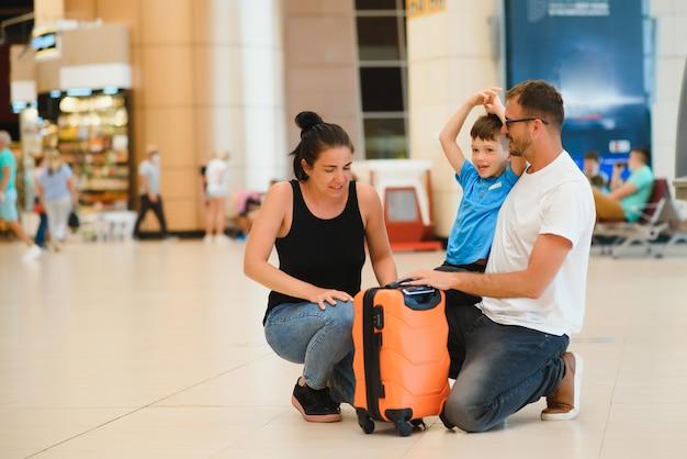 Портрет путешествующей семьи с чемоданами в аэропорту