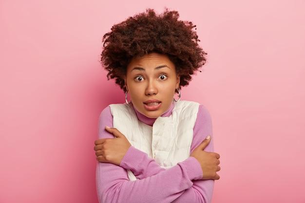 震えている巻き毛の女性の肖像画は、寒さから震え、腕を組んで、歯を食いしばって、ピンクの背景の上に分離されたカメラを驚くほど見ています