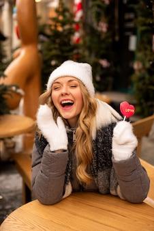 Портрет девушки красоты тенденции, которая держит леденец на палочке фигуры сердца и смеется.