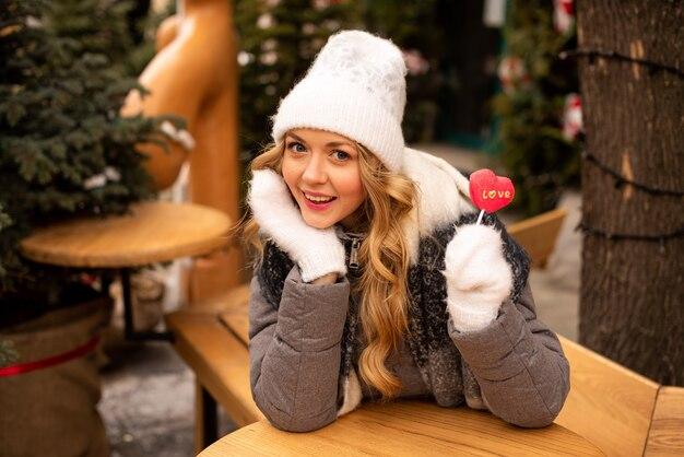 Портрет девушки красоты тенденции, которая держит леденец на палочке фигуры сердца.
