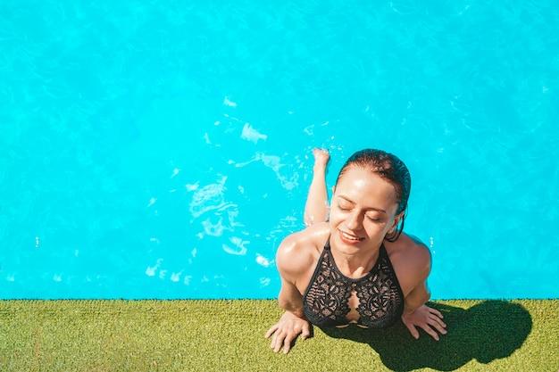 Портрет модной подходящей девушки в купальной одежде с закрытыми глазами, наслаждаясь солнечным светом отдыха на фоне голубой воды, концепция путешествия поездки, путешествия, туризма. пустое место для тестирования и дизайна.