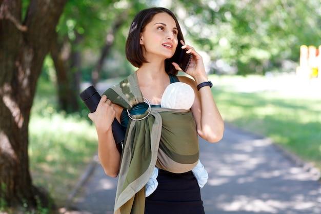 도시를 따라 걷는 슬링에 아기 아들을 입은 트렌디한 여성의 초상화 babywearing 무료 손