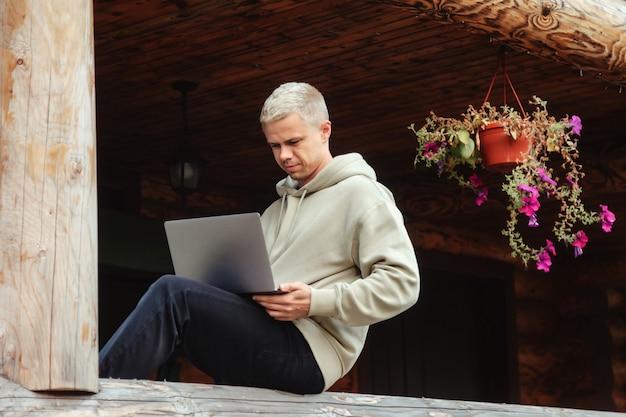 Портрет модного молодого бизнесмена с открытой террасой ноутбука загородного дома. трудоголик в домашней повседневной одежде, работает в отпуске. творческое вдохновение и запуск бизнеса. копировать пространство
