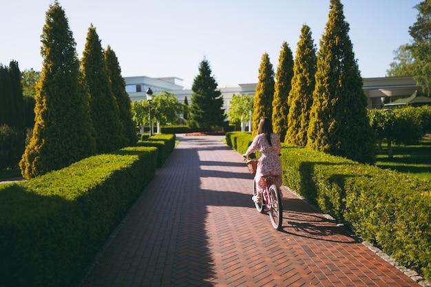 購入、屋外での食べ物や花、春や夏の公園でのゴージャスな女性のレクリエーション時間のためのバスケットとビンテージバイクの路地に乗って長いピンクの花柄のドレスを着たトレンディな若い女性の肖像画。
