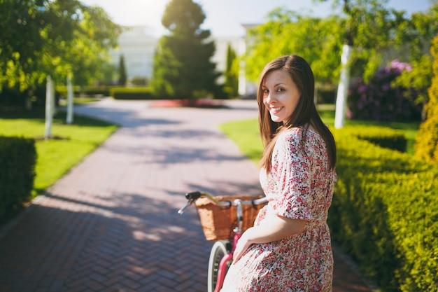 長いピンクの花柄のドレスを着たトレンディな若い女性の肖像画は、購入のためのバスケット、屋外での食べ物や花、春や夏の公園でのゴージャスな女性のレクリエーション時間のためにビンテージバイクに乗るのをやめます。