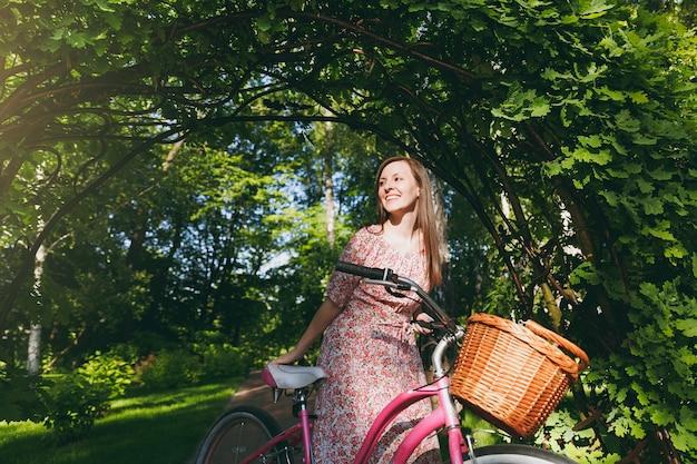 長いピンクの花柄のドレスを着たトレンディな若い女性の肖像画は、購入のためのバスケット、屋外での食べ物や花、春や夏の公園でのかわいい女性のレクリエーション時間のために自転車でオークのアーチの下に乗るのをやめます