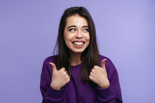 Портрет модной молодой женщины показывает палец вверх над фиолетовым