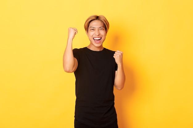 自信を持ってアジア人男性、ガッツポーズ、笑顔で勝利の肖像画