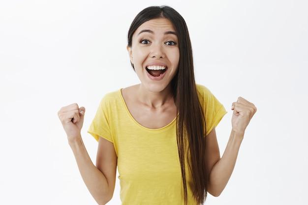 Портрет торжествующей радостной и красивой девушки в желтой футболке, поднимающей сжатые кулаки, изумленный и удивленный победой