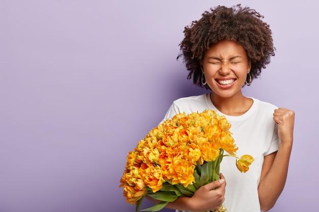 肌の色が濃い勝利の女性の肖像画、恋人から素敵な花束を受け取り、拳を握りしめ、楽しく笑う