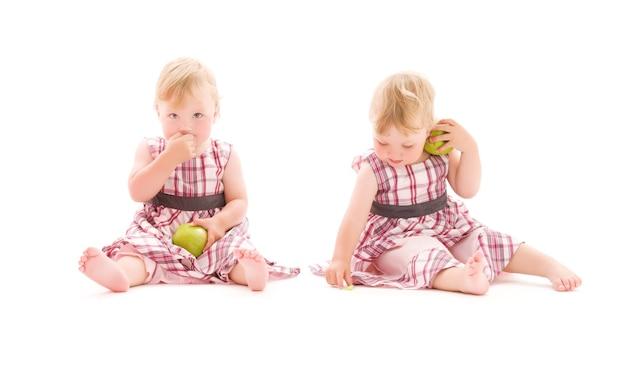 白い壁の上の2つの愛らしい双子の肖像画