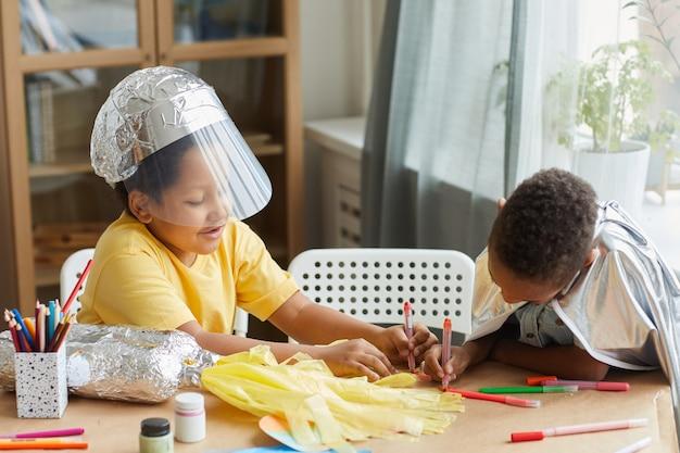 Портрет двух афроамериканских мальчиков, играющих в космонавтов и шящих скафандры, во время урока искусства и ремесел в дошкольном учреждении или центре развития