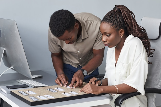 オフィスで一緒に働いている間チャートを行うことを計画している2人のアフリカ系アメリカ人のビジネスマンの肖像画