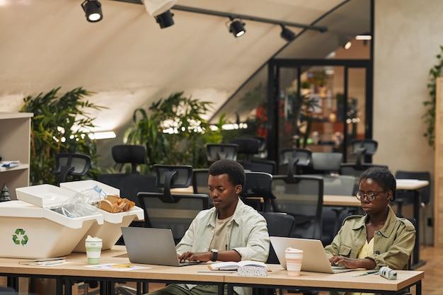 현대 사무실에서 쓰레기 분류 쓰레기통으로 작업하는 동안 노트북을 사용하는 두 명의 아프리카 계 미국인 사람들의 초상화, 복사 공간