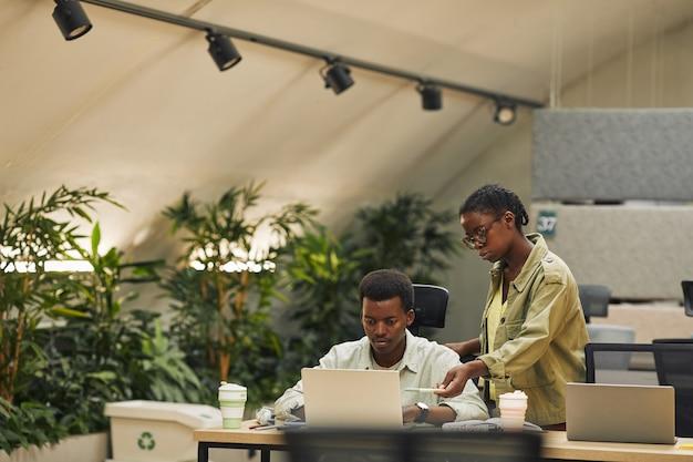 Портрет двух афроамериканцев, работающих в современном офисе с открытым пространством, фокус на женщине-менеджере, инструктирующей стажера или коллегу, копирование пространства