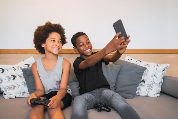 自宅で携帯電話で自分撮りをしている2人のアフリカ系アメリカ人の兄弟の肖像画。ライフスタイルとテクノロジーのコンセプト。