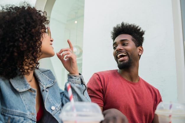 Портрет двух афро-друзей, весело проводящих время вместе и хорошо проводящих время, попивая свежий фруктовый сок на открытом воздухе в кафетерии.