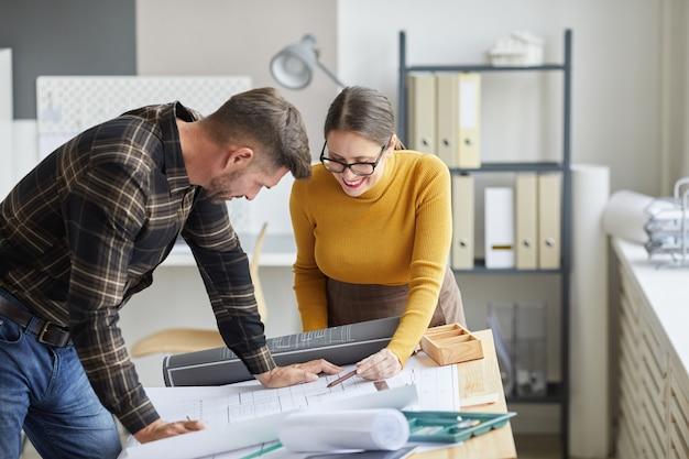 Портрет двух архитекторов, сотрудничающих над чертежами, стоя у чертежного стола и вместе работающих в офисе,