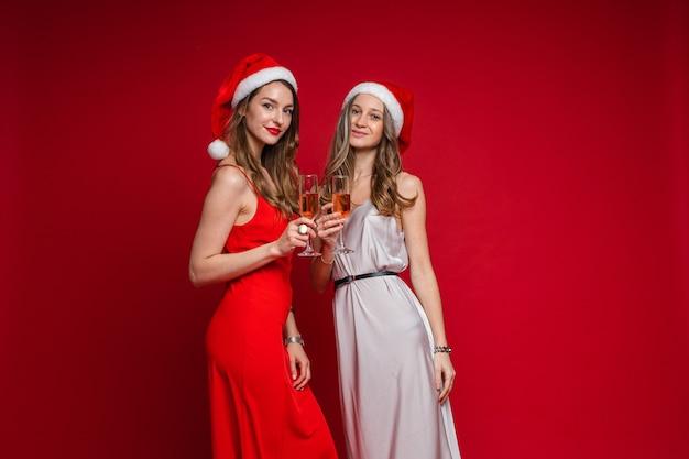 Портрет двух привлекательных подружек с длинными волнистыми волосами в красных и белых шелковых платьях, позирующих в шляпах санты с бокалами розового вина