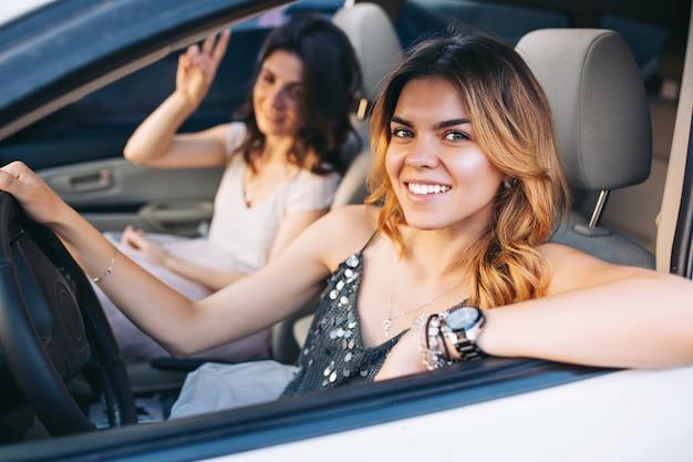 車を運転する2人の魅力的な女の子の肖像画。彼らは笑っている。