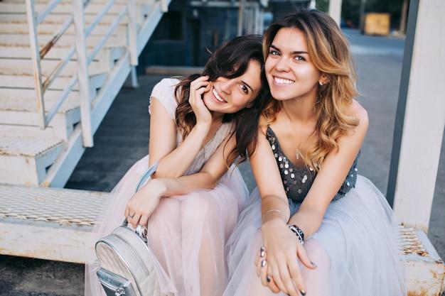 屋外の階段に座っているチュールスカートの2人の魅力的な女の子の肖像画。彼らは笑っている。