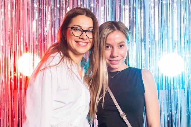 ハグと銀色の光沢のある背景に分離されたカメラを見てイブニングドレスで2つの魅力的な幸せな女性の肖像画。誕生日パーティー、休日、夜のクラブのコンセプト。