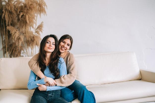 Портрет двух лучших друзей привлекательных женщин, сидящих на диване, обнимаются друг с другом