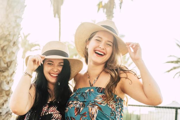 夏休みに屋外で麦わら帽子をかぶっている2人の美しく陽気な女性の友人の肖像画。麦わら帽子をかぶった楽しいファッショナブルな女性観光客