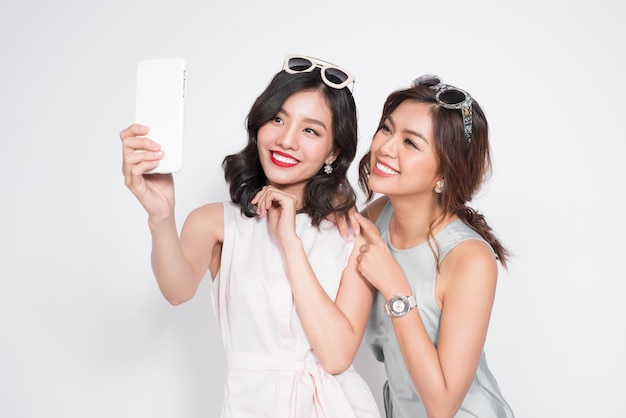 セルフィーを取る2人の美しいアジアのファッショナブルな女性の肖像画