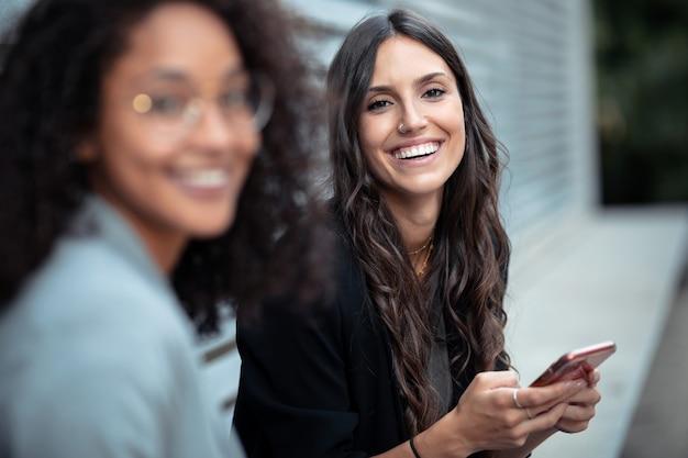 Портрет двух красивых женщин-предпринимателей, использующих смартфон, глядя на камеру, сидя на скамейке на улице.