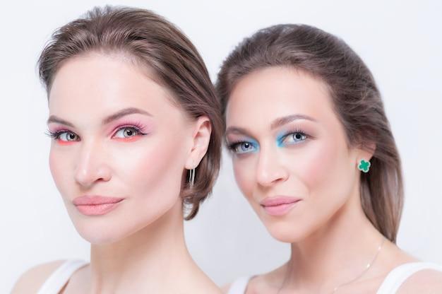 白い背景の上の反抗的な化粧をした2人の美しい女の子の肖像画。女性の友情の概念。高品質