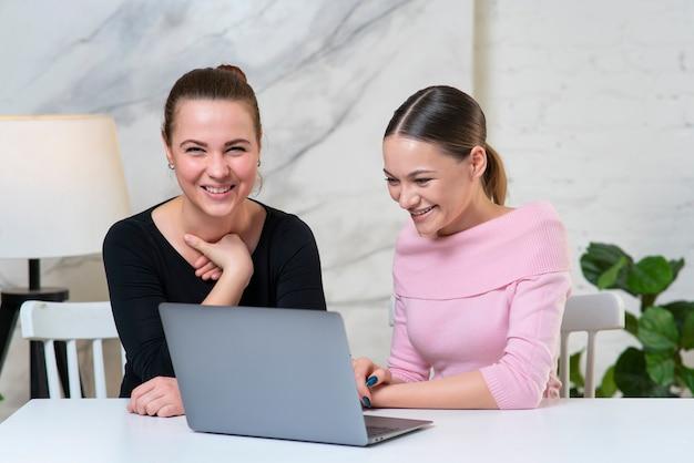 Портрет двух красивых счастливых веселых позитивных женщин-друзей, коллег работают вместе