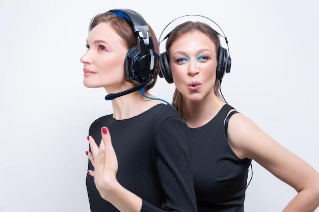 ヘッドセットを持つ2人の美しい女性の肖像画。テクニカルサポートの概念。ミクストメディア