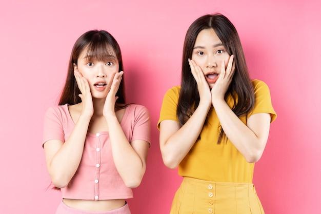 ピンクの壁にポーズをとって2人の美しい若いアジアの女の子の肖像画