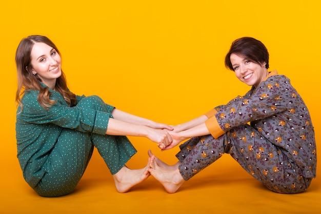 Портрет двух красивых молодых девушек в ярких пижамах, развлекающихся во время ночевки, изолированные