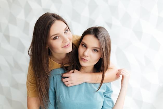 Портрет двух красивых молодых сестер-близнецов, стоящих и обнимающихся вместе