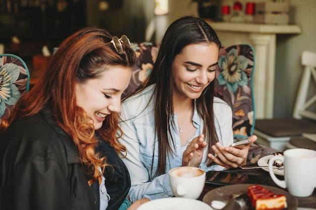 두 아름 다운 젊은 여자는 커피 숍에 앉아 인터넷에서 탐색 웃 고 그들의 스마트 폰보고의 초상화.