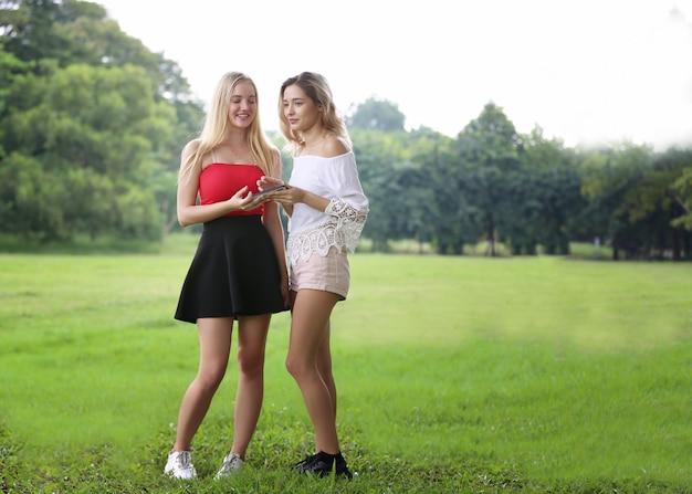 Портрет двух красивых молодых женщин, стоящих в парке