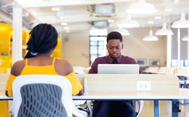 ネットブックを家のインテリアに座っている2人の黒人学生の肖像画、情報の検索と予約にラップトップコンピューターを使用しているアフリカ系アメリカ人