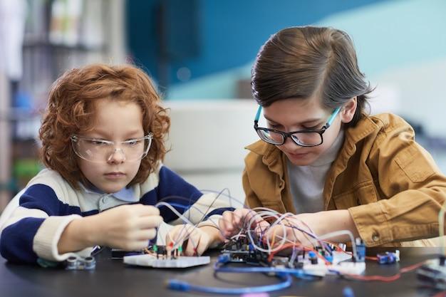 学校の工学の授業でロボットを作り、電気回路を実験している2人の少年の肖像画