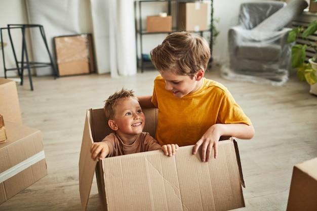 Портрет двух мальчиков, играющих в большой картонной коробке, когда семья переезжает в новое место для копирования дома